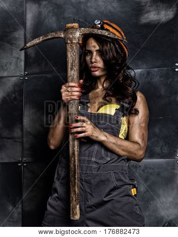 sexy female miner worker with pickaxe, in coveralls over  body.