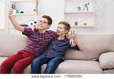 Technology, friendship and communication concept - two cute teenage boys taking selfie while posing with smile to phone and sitting on the couch in living room at home