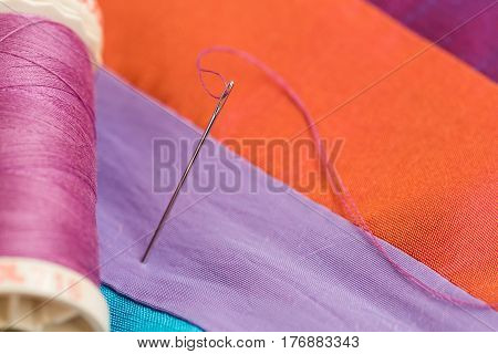 Thread passing through needle eye, close-up on orange background. the coil of violet threads on colorful fabric, macro. production of patchwork quilt, handmade. sewing process by a needle.