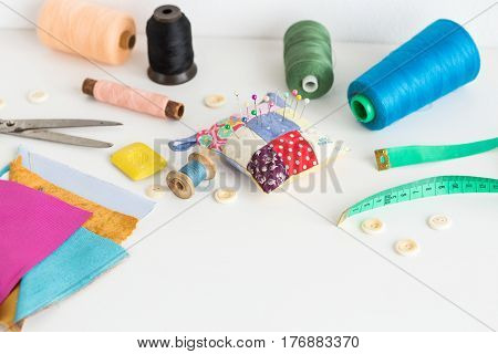 Sewing tools including fabric, scissors, needles, pins, spools of different color thread, measure tape, buttons on a white background with a empty space for the text. Sewing tools fashion design.