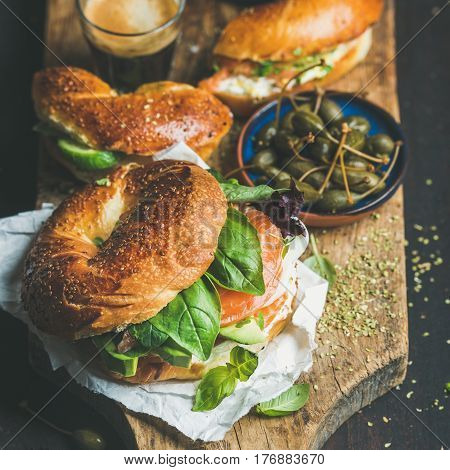 Breakfast with bagels with salmon, avocado, cream-cheese, basil, espresso coffee, capers on rustic wooden board over dark scorched background, selective focus, square crop. Healthy, diet food concept