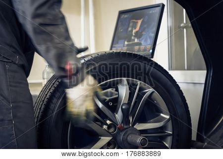 Mechanic worker makes computer wheel balancing on special equipment machine tool in auto repair service