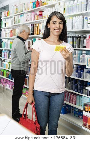 Portrait Of Smiling Customer Holding Product In Pharmacy