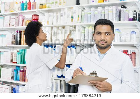 Male Pharmacist Holding Clipboard While Colleague Arranging Stock
