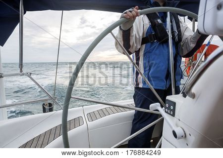 Midsection Of Man Steering Wheel Of Yacht In Sea