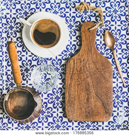 Black Turkish or Eastern style coffee in cup and cezve and wooden board with copy space, oriental Moroccan patterned background, top view