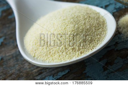 Raw unprepared semolina in white spoon. blue rural background in the style of Shabby Chic