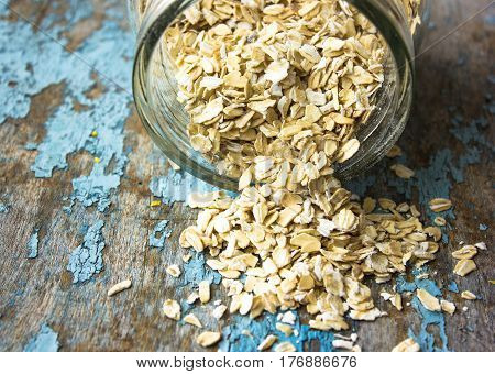 raw oatmeal is scattered on the desk of the bank in which the oat flakes are stored. blue rural background in the style of Shabby Chic. white spoon with uncooked oatmeal