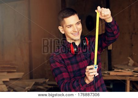 Smiling Workman Dressed In The Checkered Shirt Working With Tape-measure At The Sawmill. Timbers On