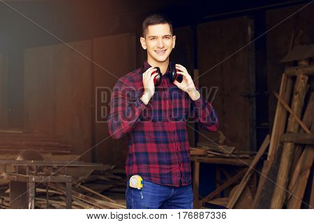 Smiling Workman Dressed In The Checkered Shirt Wearing Protective Headphones At The Sawmill. Timbers