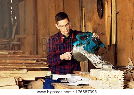 Workman Dressed In The Checkered Shirt Checking The Circular Saw At The Sawmill. Timbers On Backgrou