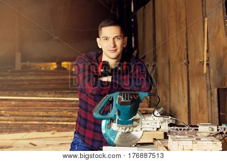 Workman Dressed In The Checkered Shirt Working With Circular Saw At The Sawmill. Timbers On Backgrou