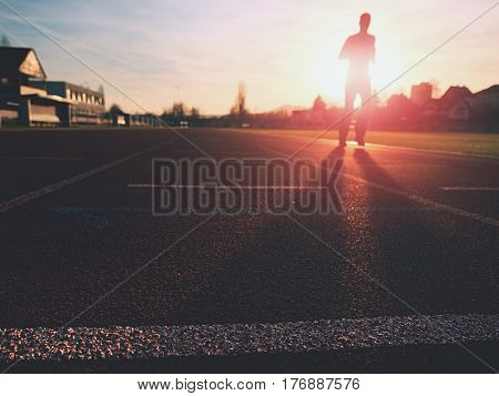 Sportsman On Running Stadium Racetrack. Adult In Evening Training