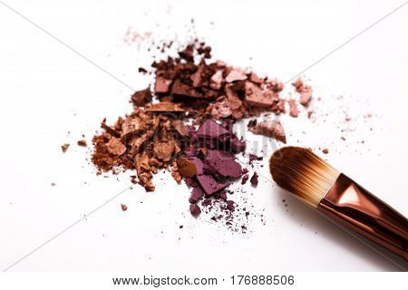 Makeup brush with blush or eyeshadow of everyday palette tones sprinkled on white. Make up and female cosmetics background