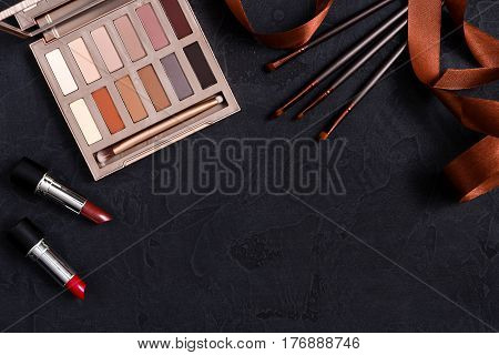 Makeup cosmetics, everyday palette frame on black background. Top view, flat lay with copy space. Beauty tools pastel beige and terracota colors collection, lipstick, brush, eyeshadow