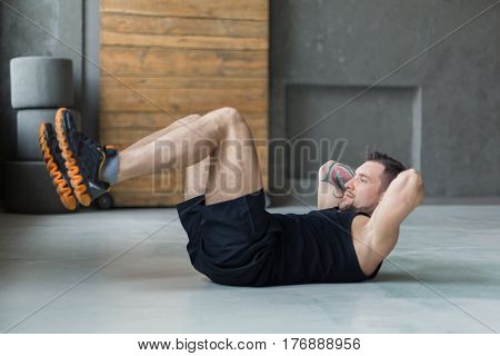 Young man workout in fitness club. Profile of caucasian guy making exercise, sit-ups and crunches for abs muscles, training indoors