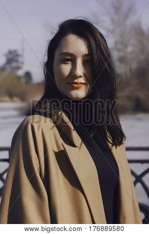 stylish young woman out for a walk. she dressed and looks very fashionable. coat of beige (camel) color and black turtleneck. beautiful woman. the portrait she smiles