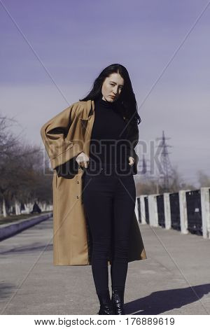 stylish young woman out for a walk. she dressed and looks very fashionable. coat of beige (camel) color and black turtleneck. beautiful woman. She pulls the black jeans.