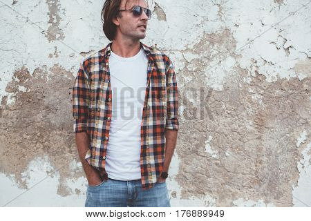 Handsome man wearing blank tshirt posing against street wall, front t shirt mock up on model, fashion urban style