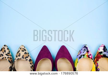 Three pairs of multicoloured stiletto shoes in different patterns on light blue background.
