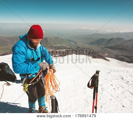 Man climber holding rope climbing equipment in mountains Travel Lifestyle concept adventure active vacations outdoor mountaineering alpinism sport