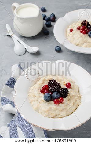 Oatmeal porridge with blueberry blackberries and currants for breakfast