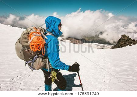 Man climber mountaineering with backpack high mountains glacier Travel Lifestyle endurance concept adventure active vacations outdoor climbing sport alpinism equipment clouds on background