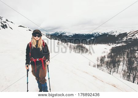 Woman climbing at snowy foggy mountains Travel Lifestyle concept adventure active vacations outdoor mountaineering sport wanderlust hiking wild nature