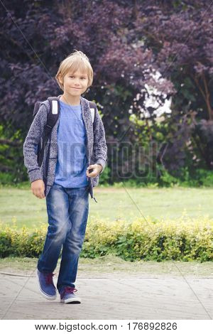 Happy schoolboy with a backpack go to school. Outdoor. Education, back to school, people concept