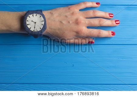 Female Hand with Watch on Blue Wooden Background
