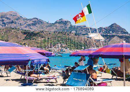 Flags Over People On Urban Beach Of Giardini Naxos