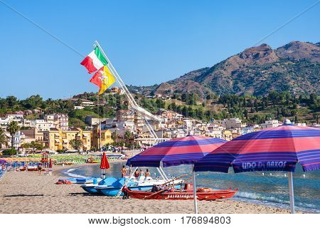 Flags Over Boats And People On Beach