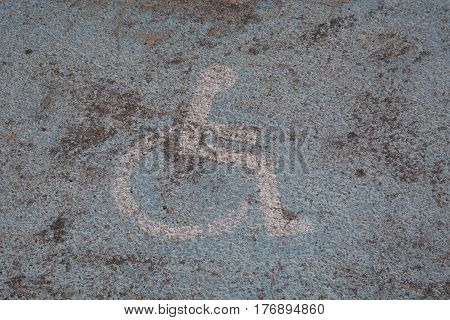 Old painted logo on the floor of a parking space reserved for the disabled