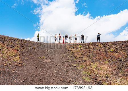 Tourists On The Edge Of Old Crater Of Etna Volcano