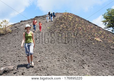 Tourists Walk On Ridge Of Old Crater Of Etna Mount