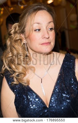 a middle-aged woman in blond evening outfit