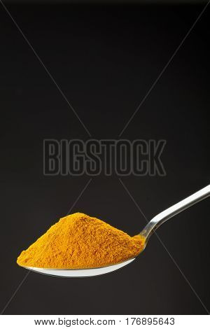 Spoon Of Ground Turmeric On Black Background