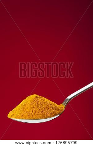 Spoon Of Ground Turmeric On Red Background