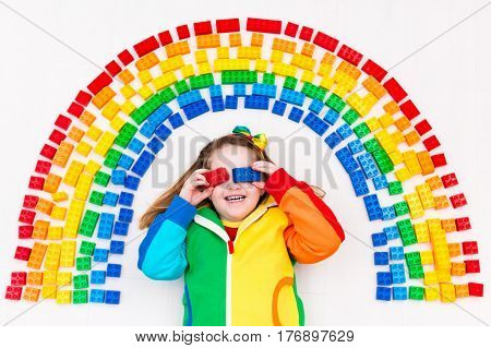 Funny little girl playing with colorful rainbow plastic blocks. Kids play create and learn colors. Educational toys for creative children. Preschooler building block toys. Kid playing on the floor.