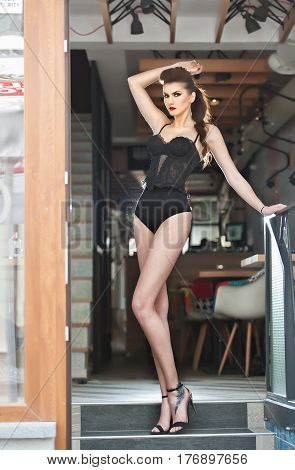 Sensual girl with long legs and high heels sitting on the chair in bar  .Handsome girl wearing beautiful body and high heels in indoor scene.Fashion model with long sexy legs