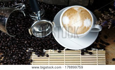 Hot cappuccino with streamed milk. Pour the hot latte art by milk. A cup of strong espresso coffee put on the wood table with shiny dark roasted Italian coffee beans. Aroma and flavor coffee beverage.
