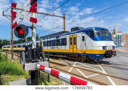 Hoek van Holland the Netherlands - July 6 2016: Dutch electric train going through crossing