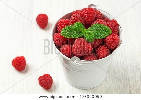 Fresh berries. Raspberry in white mini bucket with fresh mint leaves on white wooden background. Diet and healthy food concept horizontal
