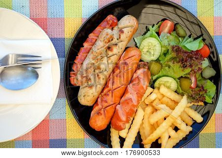Sausage fried and french fries with vegetables on chintz.