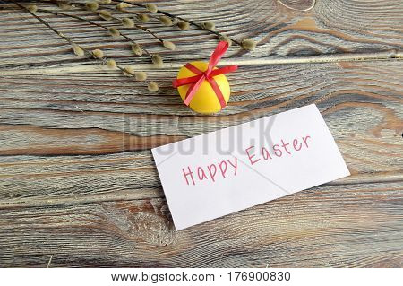 Easter color egg and willow is a holiday symbol. Egg is tied up by a red tape. Egg, a willow and a note with a wish are on a wooden table