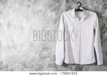 White Shirt With Long Sleeves On Grunge Background. Free Space For Text