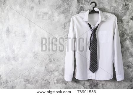 White Shirt With Long Sleeves And Necktie On Grunge Background. Free Space For Text
