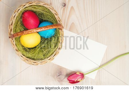 Easter eggs in basket on the rustic wooden planks. Spase for text. Top view.