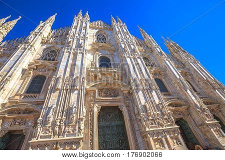 Gothic church facade in Piazza Duomo square of Famous Milan Dome against a blue sky at midday.