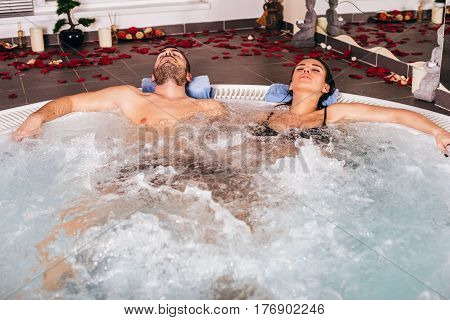 Young Attractive Couple Relax In Hot Tub